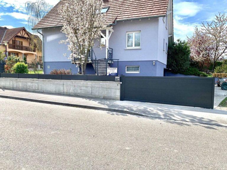 Portail coulissant bas en biais ( en pente ) avec sa clôture et BAL assorti . Portail : Karantan ( lames xxl de 300 mm ) en noir sablé 2100 .